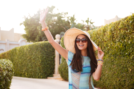 Smiling Brunette Woman in beachwear which posing near the bushes and waving away 版權商用圖片