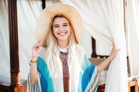 beachwear 및 골방에서 포즈를 취하고 카메라를 찾고 모자에 웃는 여자 스톡 콘텐츠