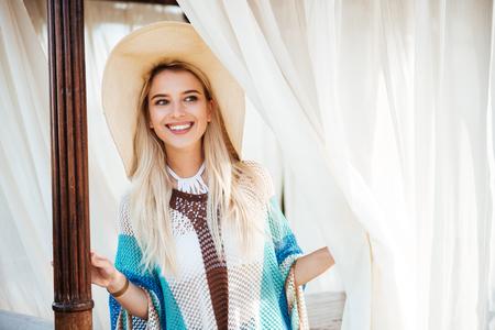 beachwear 및 골방에 포즈를 취하 고 멀리 찾고 모자에 행복 한 여자