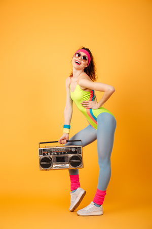 Full length of attractive young sportswoman standing and posing with retro boombox over yellow background Stock Photo