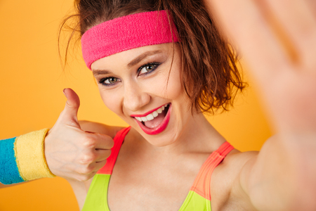 Happy young woman athlete making selfie and showing thumbs up over yellow background Stock Photo