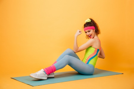 laying abs exercise: Smiling beautiful young sportswoman doing exercises for abdominal muscles on mat over yellow background