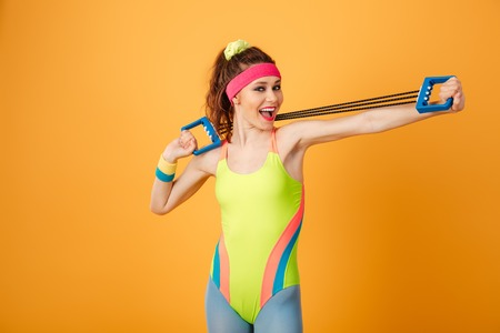 Smiling beautiful young sportswoman doing exercises with expander over yellow background