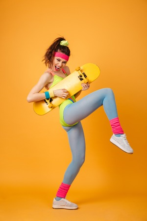 Cheerful playful young fitness woman holding skateboard and having fun over yellow background Stock Photo