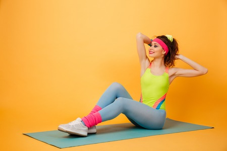 laying abs exercise: Cheerful pretty young woman athlete training and working out on mat over yellow background Stock Photo