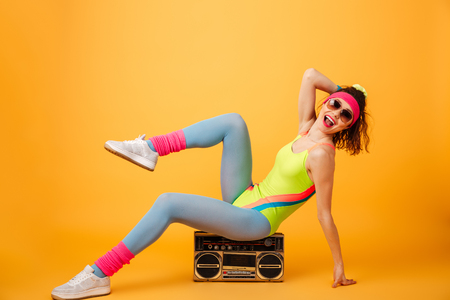 Cheerful charming young fitness woman in sunglasses sitting and posing on boombox over yellow background