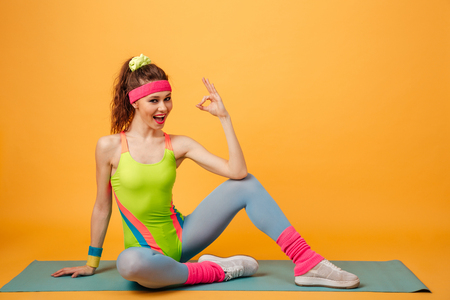 Happy cute young sportswoman sitting on mat and showing ok gesture over yellow background