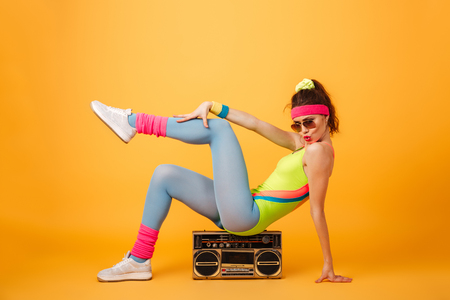 Attractive playful young woman athlete sitting on retro boombox and posing over yellow background Stock Photo