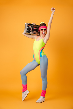 Full length of happy young sportswoman holding old boombox and shouting over yellow background
