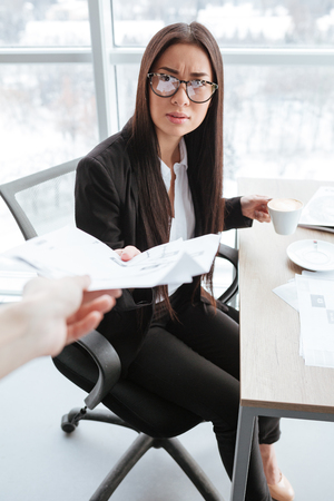 analytic: Serious asian young businesswoman in glasses receiving documents and drinking coffee at the table Stock Photo