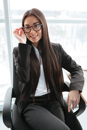 Bella giovane donna di affari asiatica felice in vetri che si siedono e che sorridono nell'ufficio