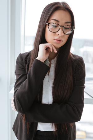 Thoughtful asian young businesswoman standing and thinking near the wndow in office