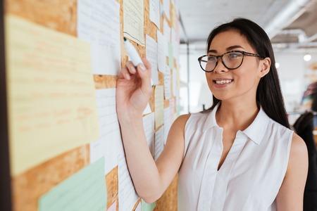 Bonne jolie jeune femme asiatique dans des verres d & # 39 ; écriture de la publicité sur le babillard Banque d'images - 76539780