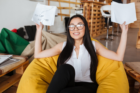 Cheerful ?ute asian young woman in glasses sitting in bean bag chair and holding papers