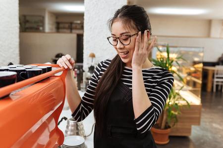 Asian barmaid in eyeglasses which standing near the coffee maker 版權商用圖片
