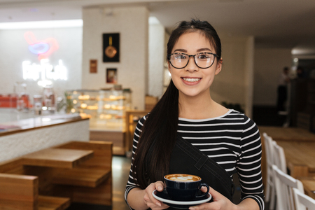 Smiling Asian barmaid with cup of coffee in hands which looking at camera