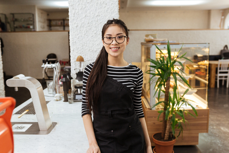Asian barmaid in eyeglasses which standing near the counter and looking at camera