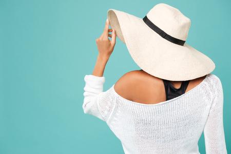 青い背景に夏帽子の美しい若い女性の背面図