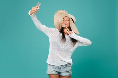 Woman in beachwear which making selfie on phone and showing peace sign at camera. Isolated turquoise background 版權商用圖片