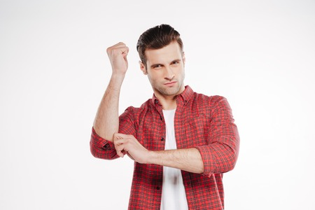 invisible: Serious man in shirt which posing in studio with invisible Nunchuck and looking at camera. Isolated white background