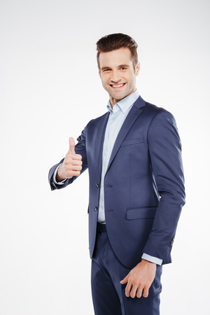 Vertical image of business man which standing in studio and showing thumb up. Isolated white background Stock Photo