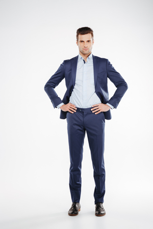 Full length portrait of business man which holding arms on hip and looking at camera. Isolated white background