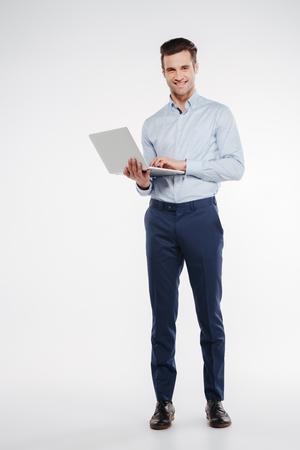 Verticaal beeld van Glimlachende bedrijfsmens die zich in studio met in hand laptop bevindt en camera bekijkt. Geïsoleerde witte achtergrond Stockfoto