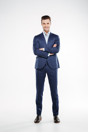 Full length image of smiling man in suit which posing in studio with crossed arms and looking at camera. Isolated white background Zdjęcie Seryjne