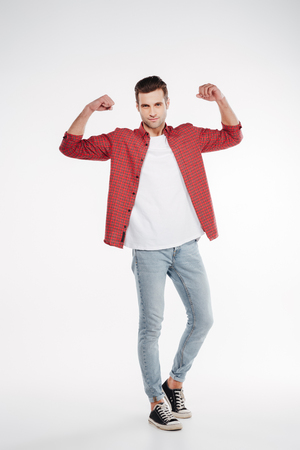 Vertical image of cool man in shirt and jeans which showing his biceps and looking at camera. Full length portrait over white background Stock Photo