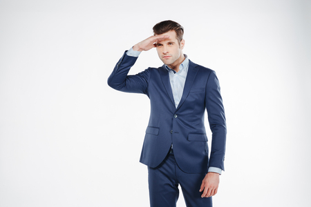Man in blue suit which peers away with hands on forehead. Isolated white background