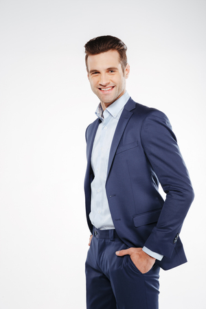 Vertical image of smiling business man which standing sideways with arms in pockets and looking at camera. Isolated white background