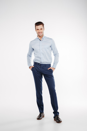 ビジネス服のポケットやカメラ目線で腕とスタジオでポーズをとっている男の縦方向のイメージ。孤立した白い背景