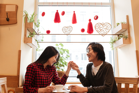 Image of smiling asian young loving couple sitting in cafe indoors drinking coffee. Looking at each other. Stock Photo - 76317573