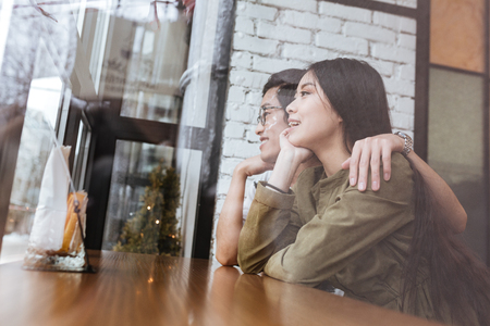 Image of happy asian young loving couple at the cafe. Looking aside. photo