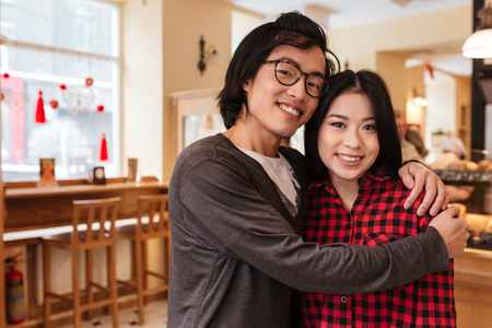 Image of smiling asian young loving couple sitting in cafe indoors. Looking at camera. photo