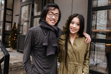 Image of happy asian young loving couple standing near cafe outdoors. Looking at camera while hugging. photo