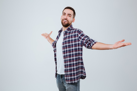 Happy Bearded man in shirt which looking at camera with hand to the sides Stock Photo