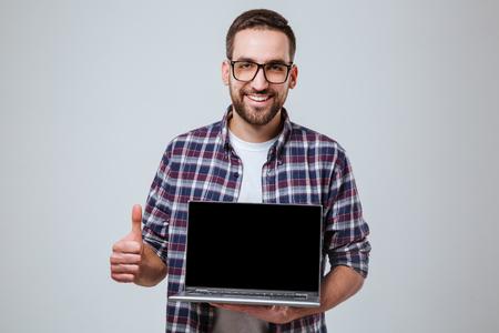 Eyeglases のひげを生やした男が示す空白のノート パソコンの画面と親指まで笑ってカメラを見ながら。孤立した灰色の背景 写真素材