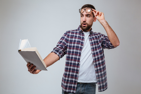Shocked Bearded man in eyeglases which reading book. Isolated gray background Stock Photo
