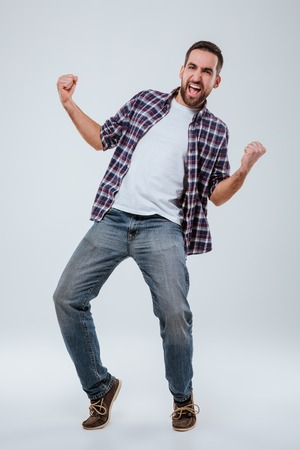 staring at the camera man: Vertical image of Screaming happy Bearded man in shirt. Full length portrait. Isolated gray background Stock Photo