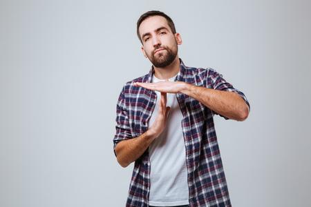 Hombre barbudo serio en la camisa que muestra la muestra del tiempo hacia fuera. Fondo gris aislado