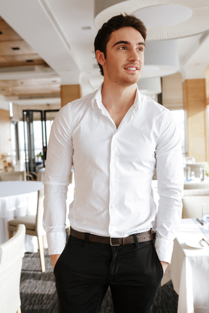 Vetical image of smiling man in business clothes which standing in restaurant with arms in pockets and looking away Stock Photo