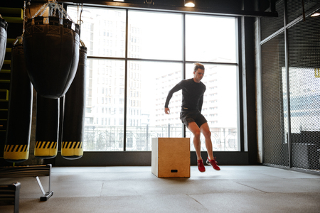 Athletic man which jumping from the box in gym with window on background Stock Photo