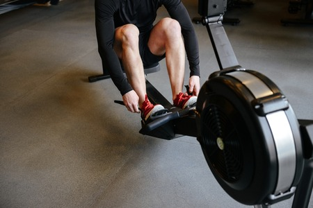 anaerobic: Cropped image of athletic man which using rowing machine in gym Stock Photo