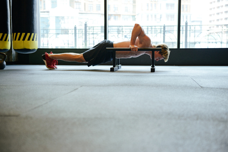 Side view of man which doing push-ups in gym with window on background