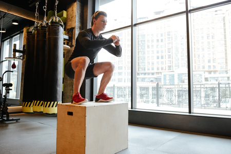 Side view of Athletic man which jumping on box in gym with window on background Stock Photo