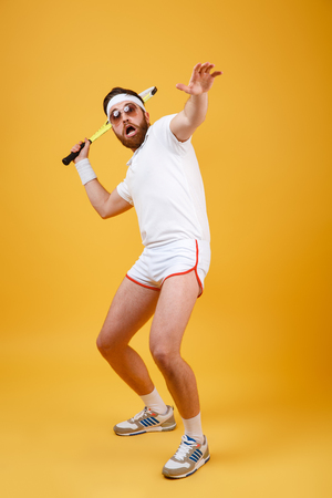 Vertical image of funny sportsman in sunglasses which playing in tennis. Full length portrait over orange background
