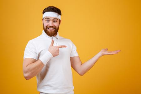 Sportif satisfait qui pointe vers le fond invisible de la fourrière. Arrière-plan orange isolé Banque d'images - 75915169