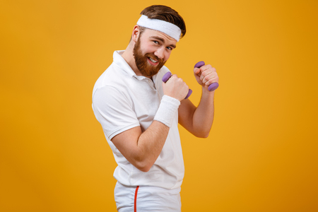 Sportsman which standing sideways while holding lightweight dumbbells in hands and looking at camera. Isolated orange background Stock Photo
