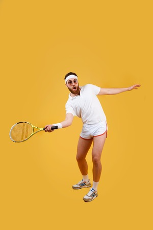 Vertical image of concentrated sportrsman in sunglasses which playing in tennis. Full length portrait over orange background Фото со стока